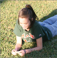 Junior, Grace Kimmel, lies on the green outside of the library to catch some rays on a sunny day.