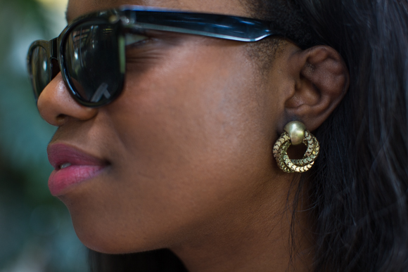 A closer look at Bianca's classic black wayfarers and her gold accent earrings.